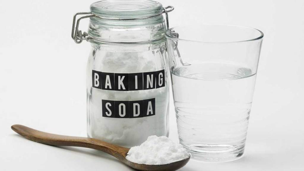 Baking soda jar beside a glass of water and a spoonful of powder