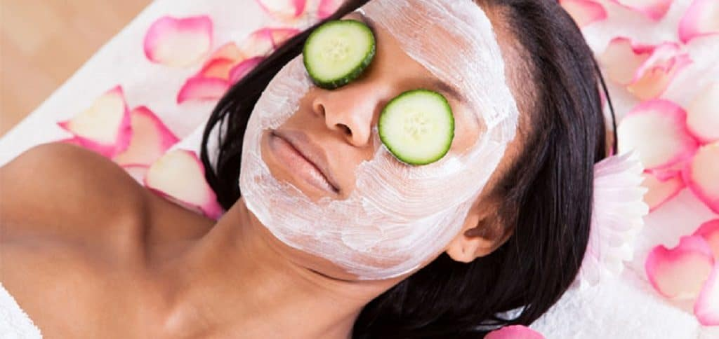 Woman lying down with a mask on her face and some cucumbers
