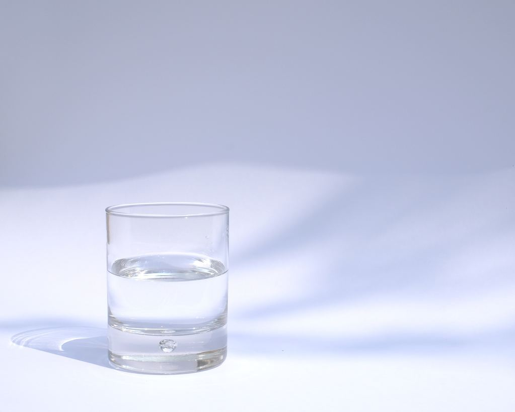 Glass of water in front of a white background