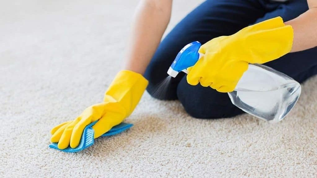 Woman wearing yellow gloves while holding a spray bottle and brush to the carpet