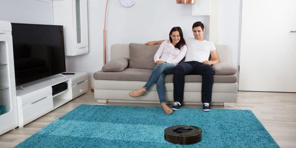 Man and woman sitting on a couch watching the robot vacuum clean