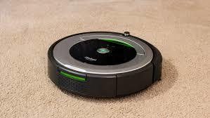 Black robot vacuum in the middle of carpet