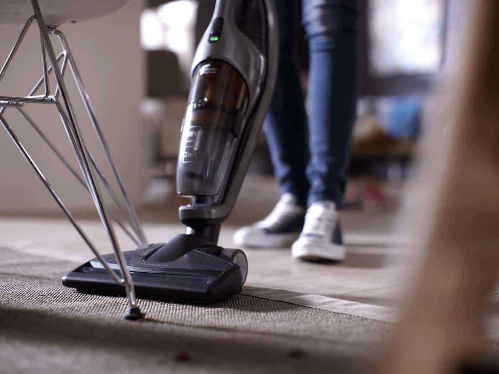 Vacuum cleaner on carpet under the table
