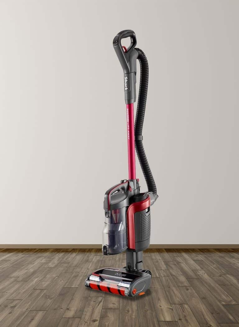 A cordless Shark vacuum in the middle of a room with hardwood floors