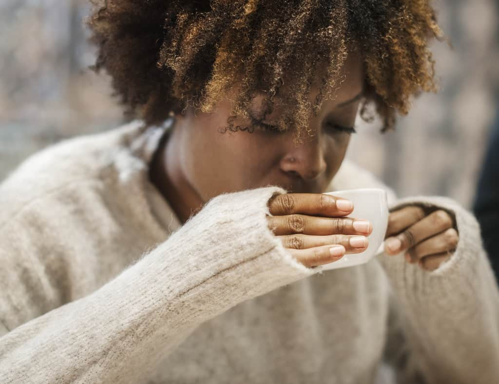 Woman sipping on a hot coffee