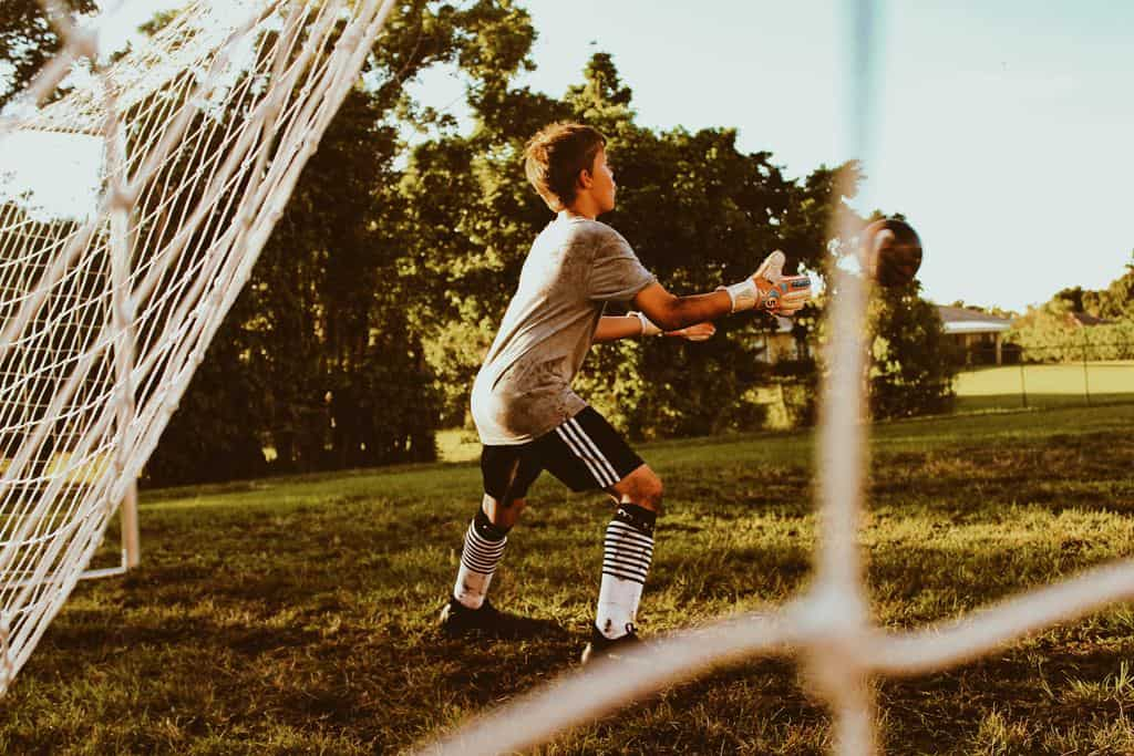 Young boy by a soccer goal receiving the ball