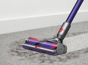 A blue Dyson Stick vacuum cleaning carpet
