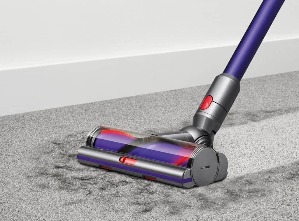 A blue Dyson Stick vacuum cleaning carpet