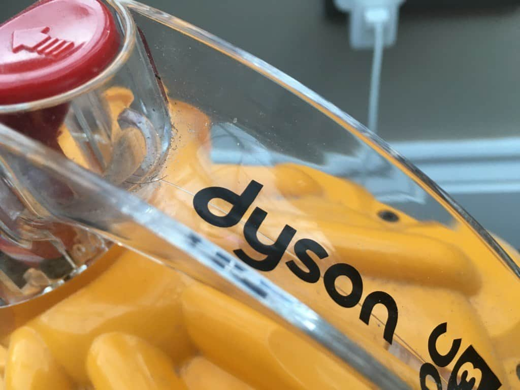 Close up of the Dyson logo on a yellow vacuum