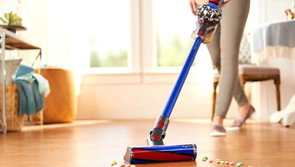 Woman cleaning her hardwood floors with a  Dyson stick vacuum