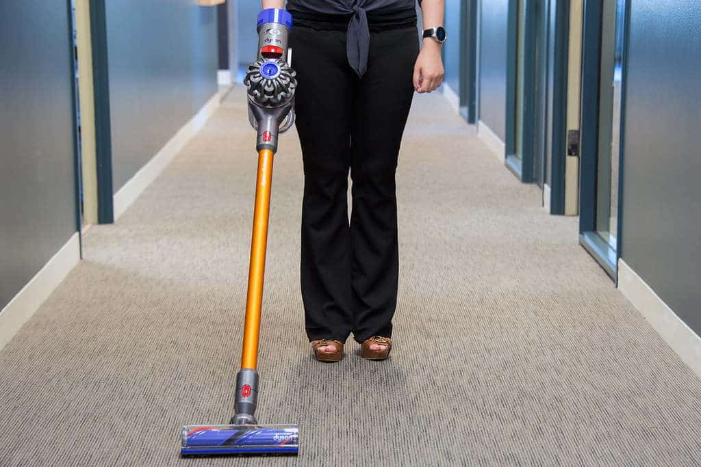 Woman in black stands with a Dyson Vacuum in hand