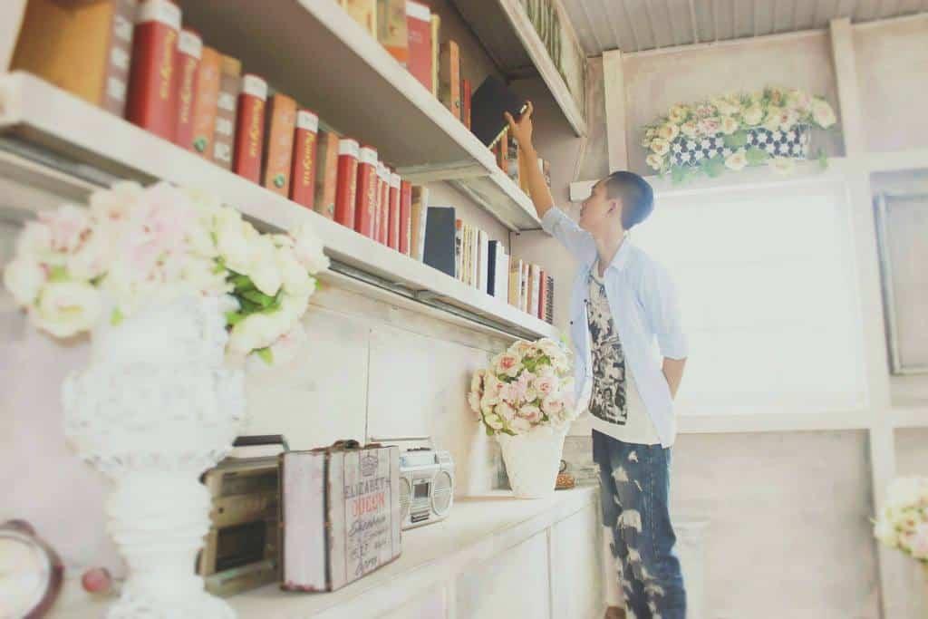 Teenager returns a book to the bookshelf