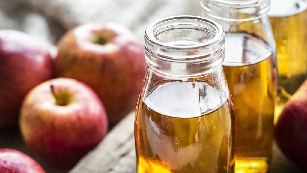 Close up of some apples and vinegar bottles