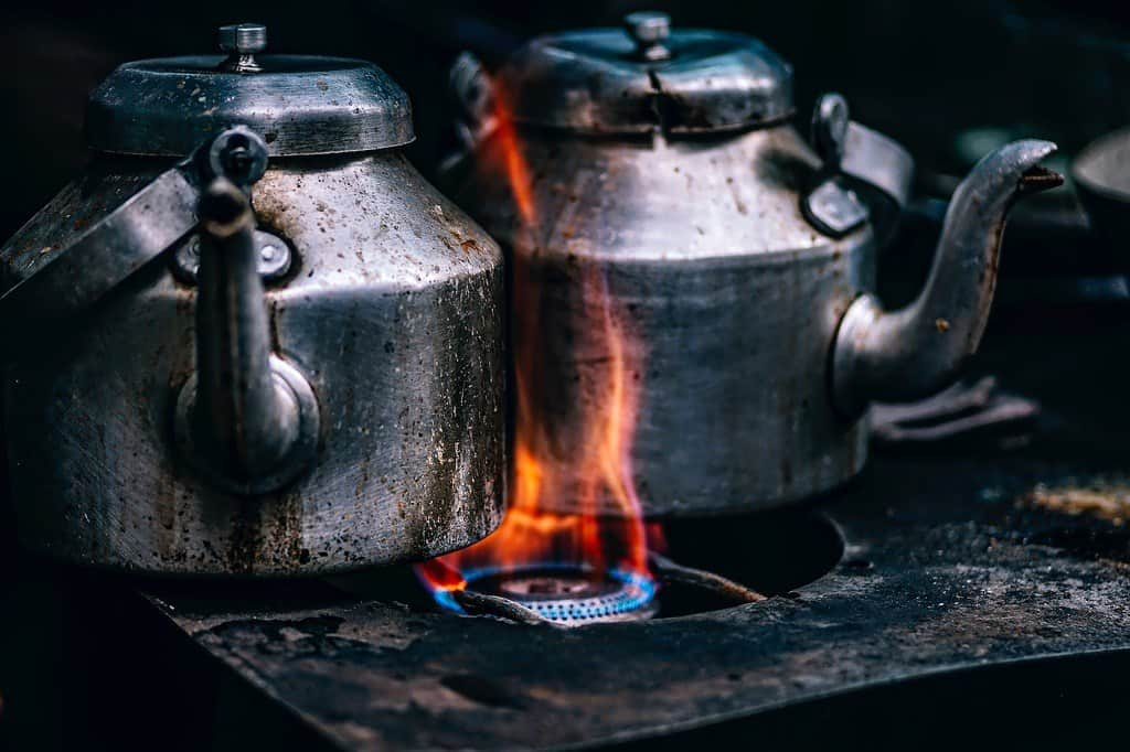 Two kettles burning on the stove