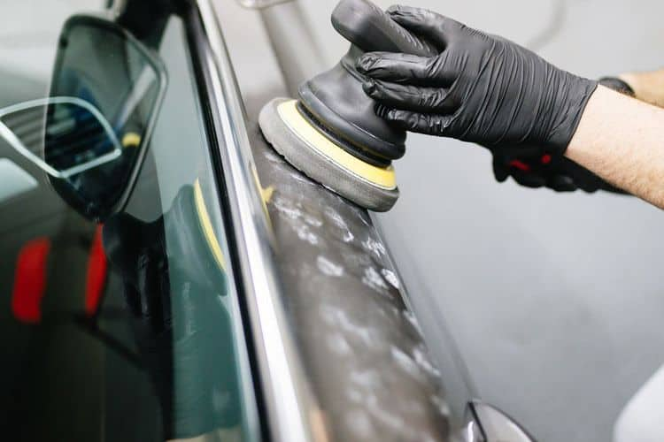 Man applying wax onto car exterior
