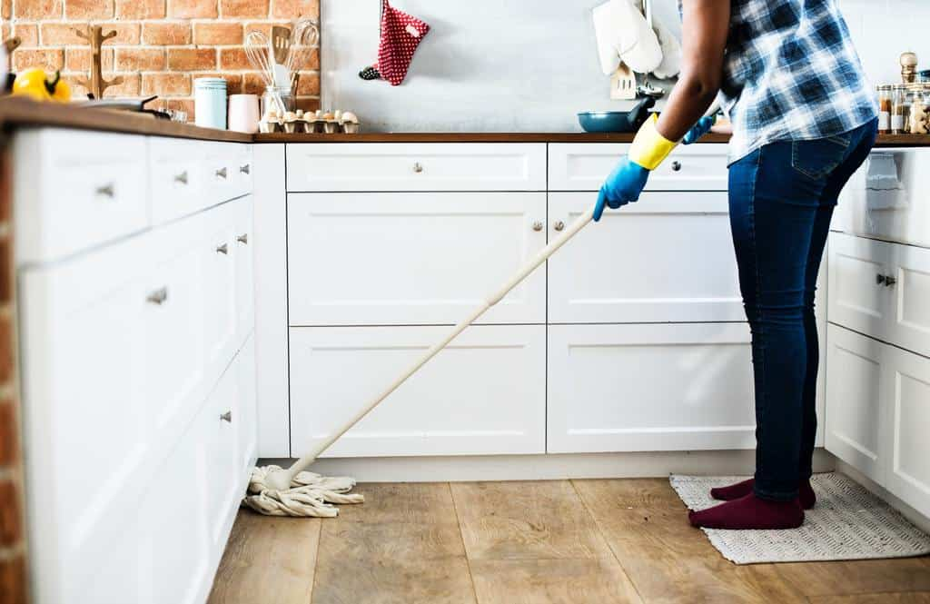 Woman cleaning her floors with a mop