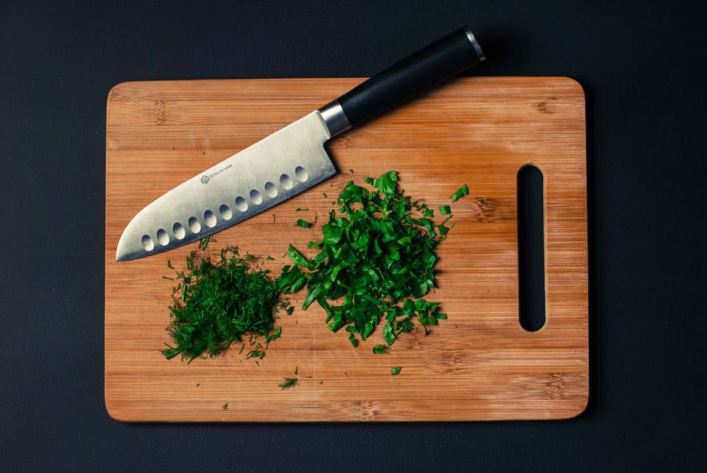 A knife on a chopping board and some herbs