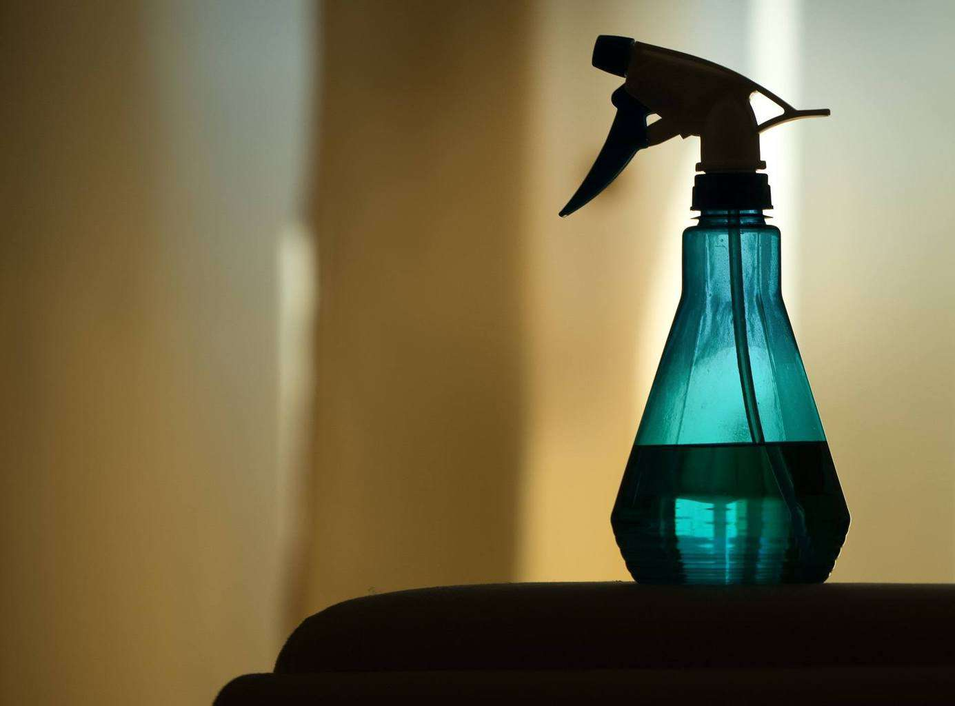 Blue spritzer bottle in front of a curtain
