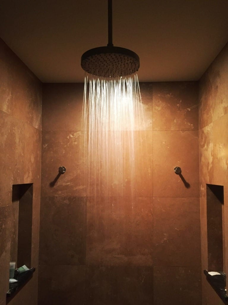 A gorgeous rainfall showerhead sits in a tile bathroom