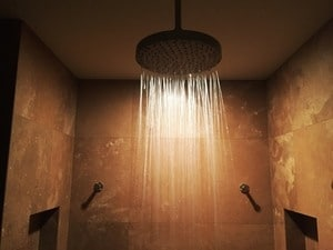 A rain shower head sprays water down from the ceiling