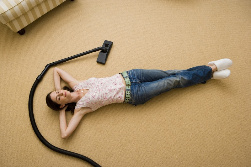 Woman lying down on floor with vacuum cleaner