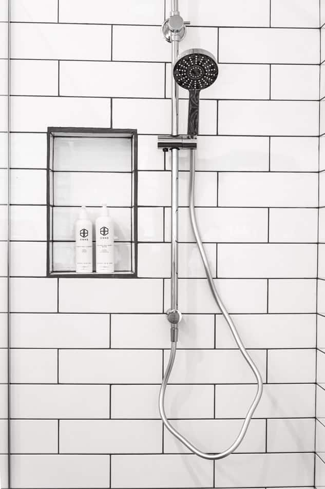Silver-colored shower with slider beside two bottles of bath products
