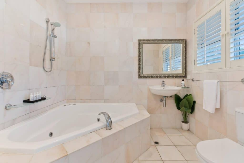 Bathroom with a handheld shower with slider and bathtub