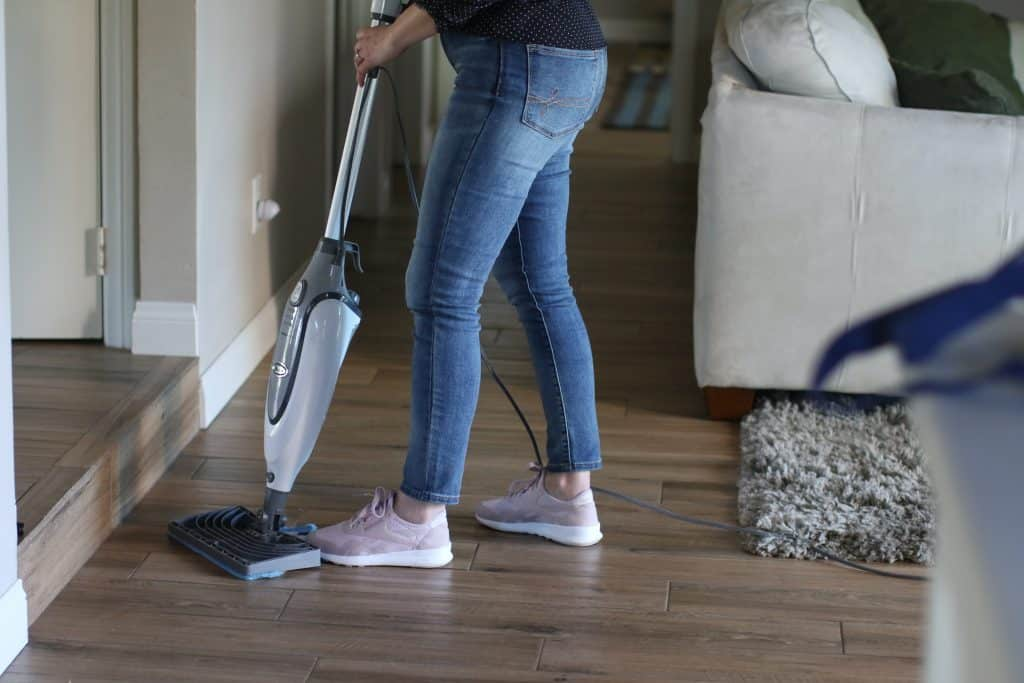 A woman cleaning the living room floor using a steam mop