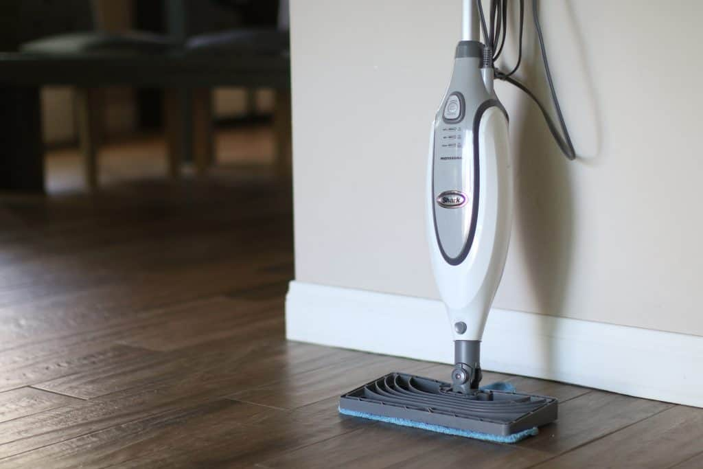 A steam mop placed against the wall