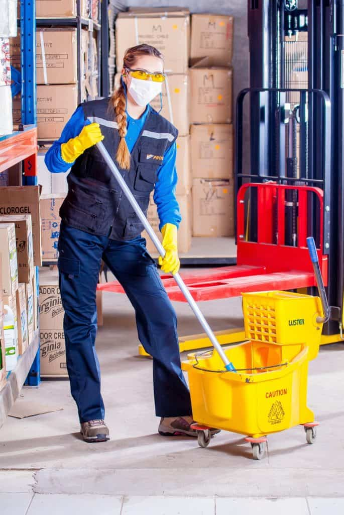 Woman cleaning her mop in a cleaning bucket