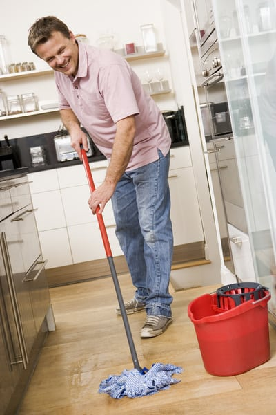Man cleaning the floor with a spin mop