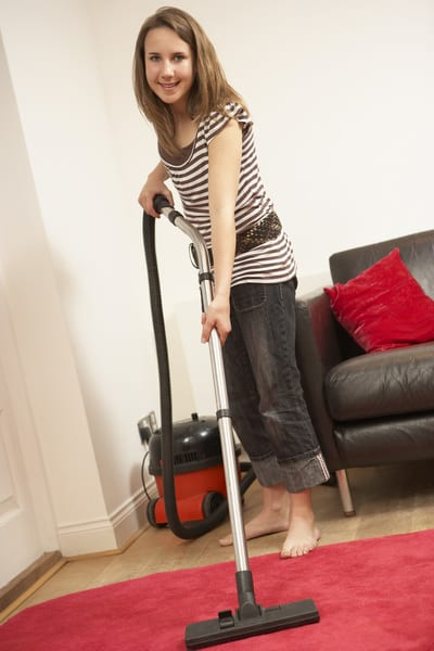 A girl using a small cylinder vacuum cleaner