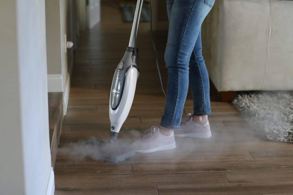 Woman using her steam mop on a vinyl flooring