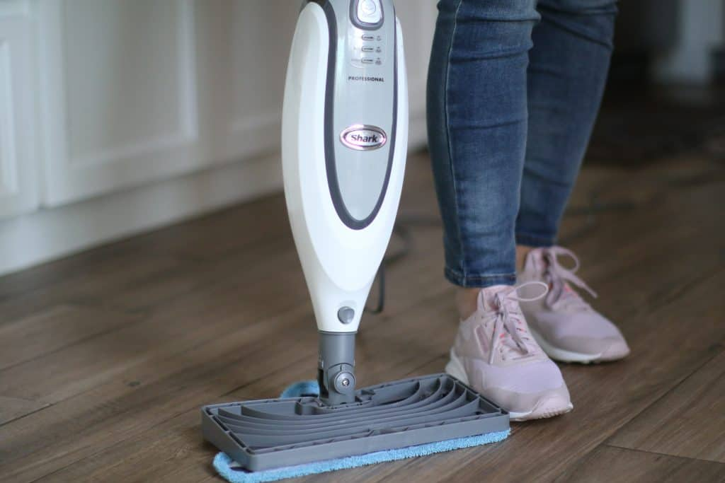 Woman using a steam mop on wooden floors
