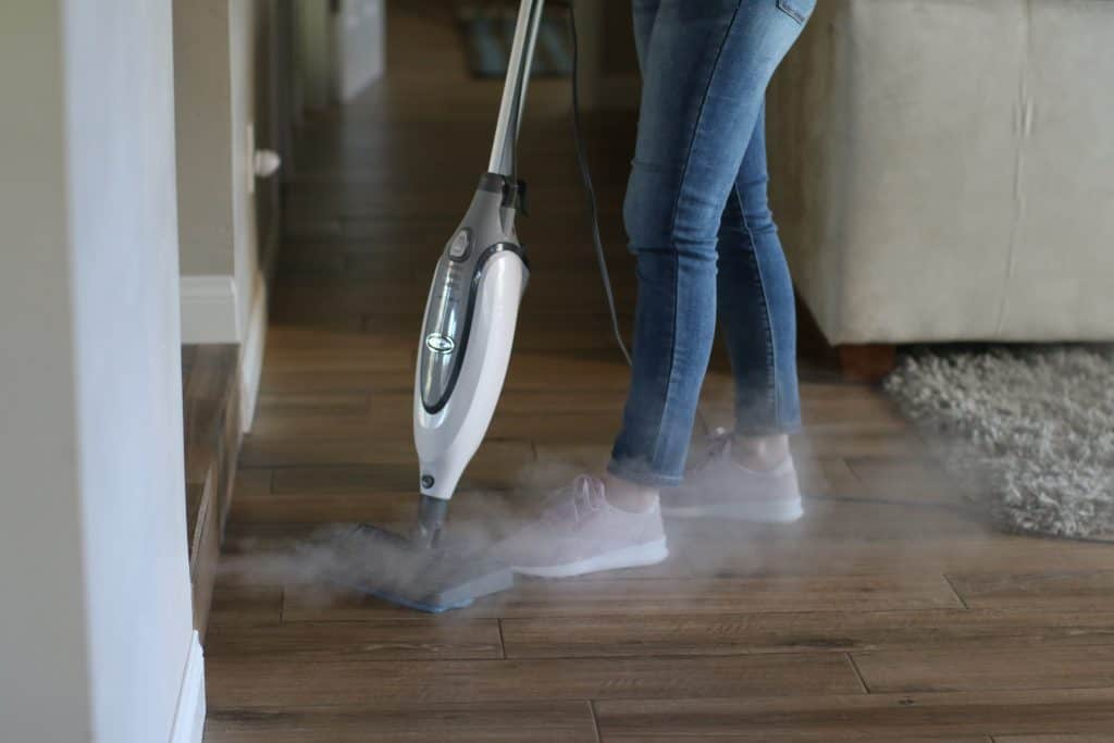 A woman cleaning the floor with a steam mop