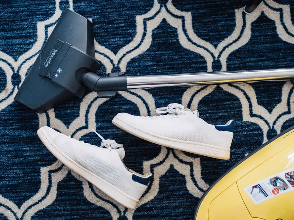 A vacuum cleaner beside a pair of white sneakers