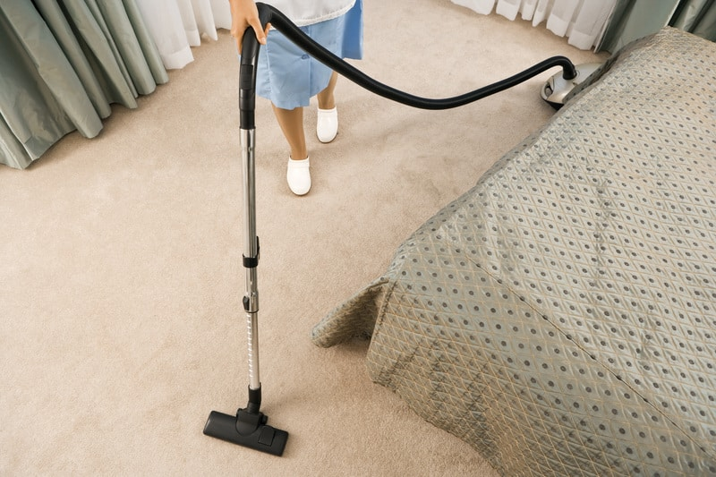 Woman cleaning a room carpet using a vacuum cleaner