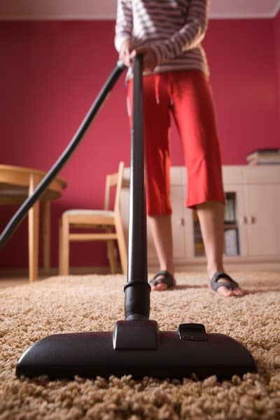 Woman cleaning a carpet using a vacuum cleaner
