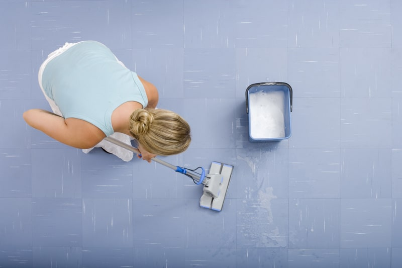 Woman using a sponge mop to clean the floor
