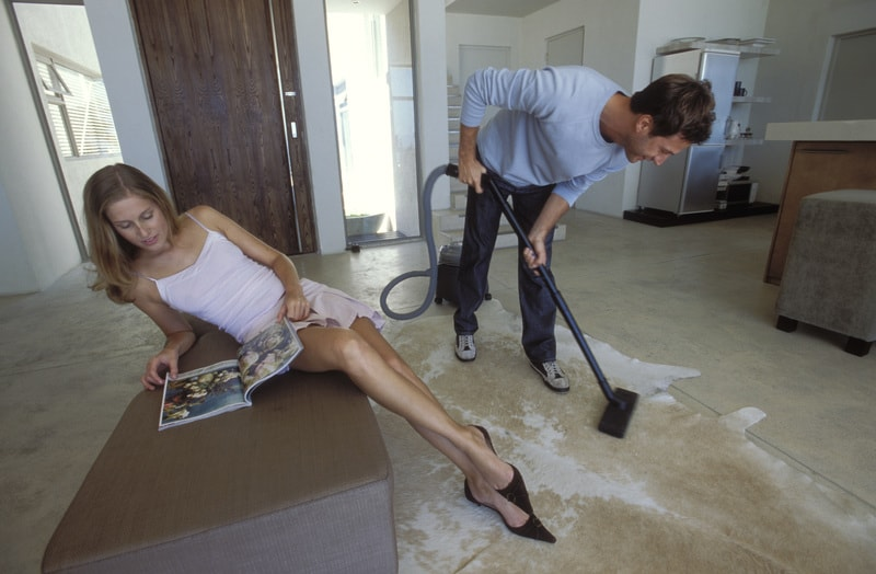 Woman reading and man vacuuming floor