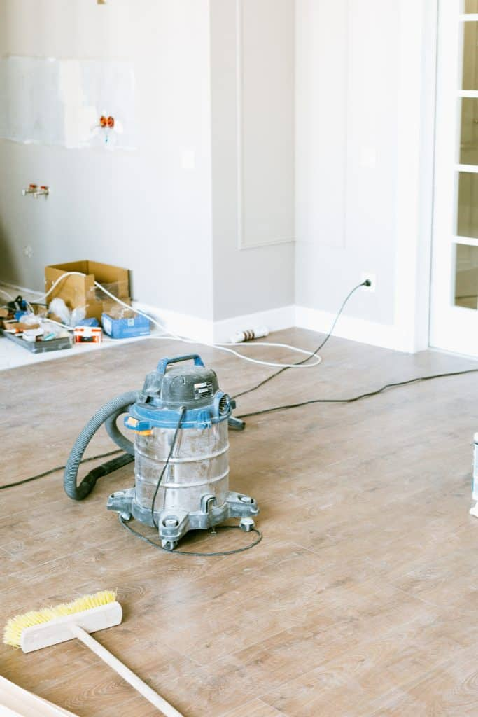 A wet dry vac being used to clean a dusty wooden floor