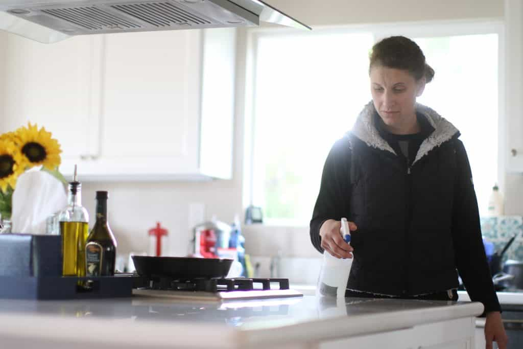 Woman spraying cleaning solution to her kitchen