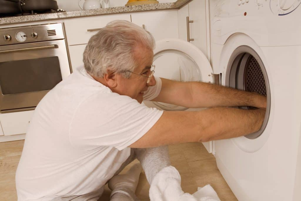 Man trying to wash a spin mop head in his washing machine