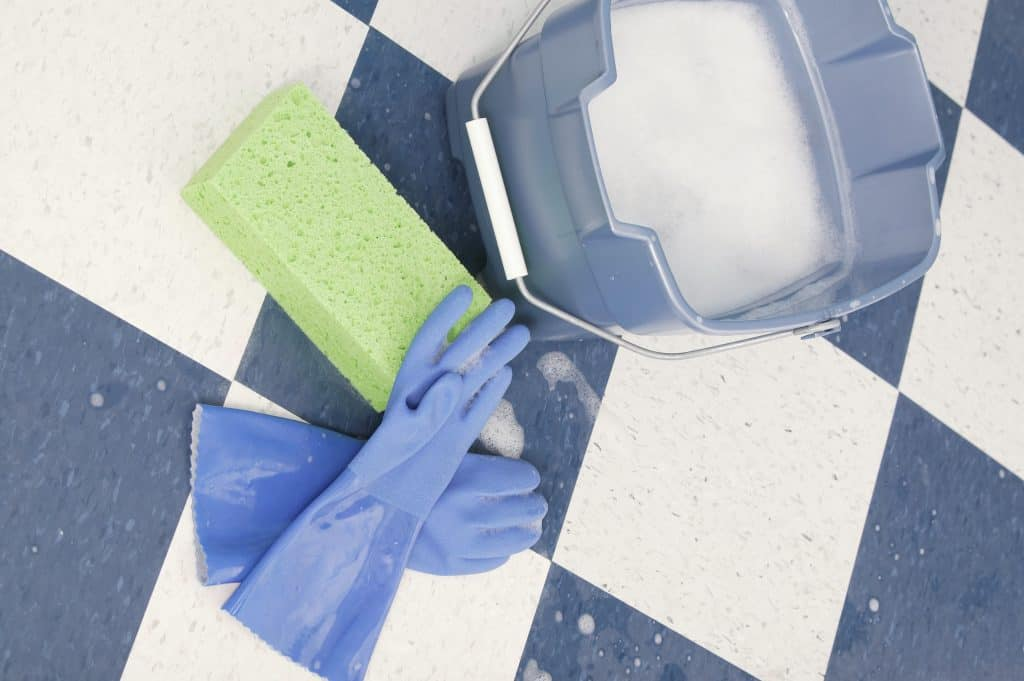A bucket of soapy water, sponge and gloves placed on the floor