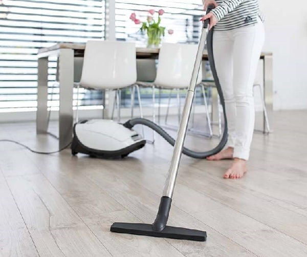 Person using a small compact vacuum to clean floor