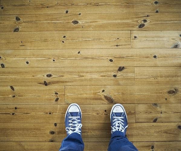 Person wearing a pair of blue sneakers standing on hardwood floor