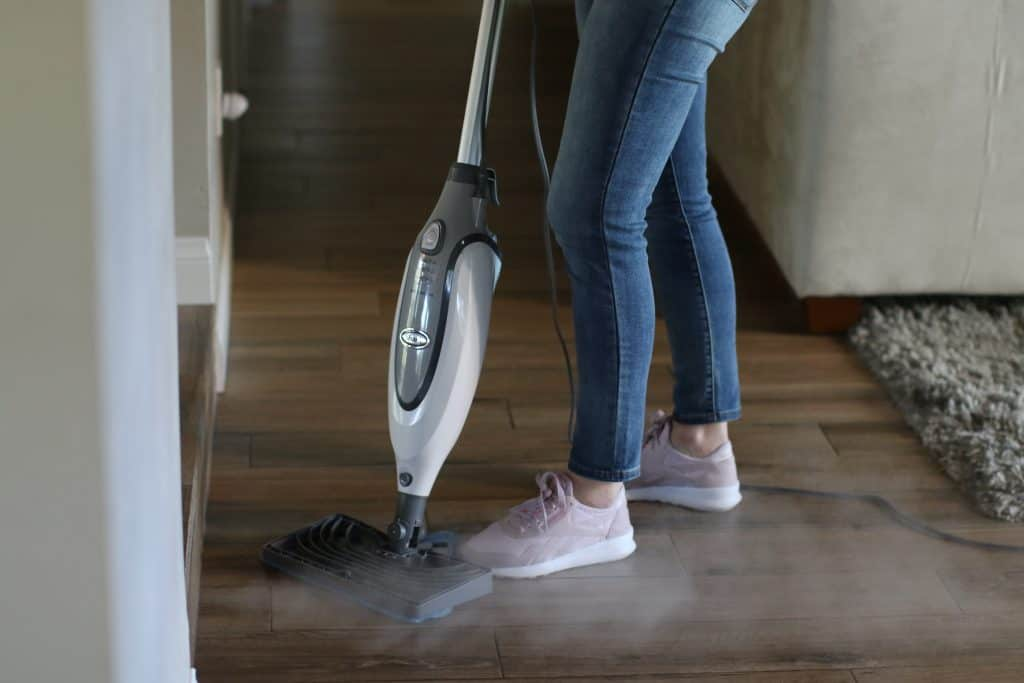 Woman using her steam cleaner to clean floor tile grout
