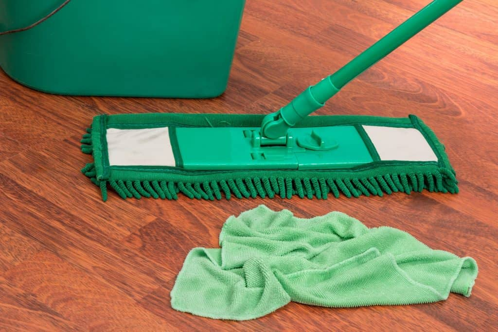 A microfiber mop, green rag and a bucket on a wooden floor