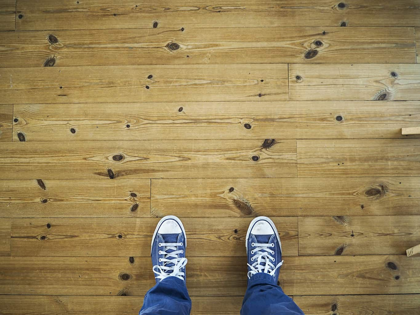 Person wearing sneakers stepping on laminated flooring