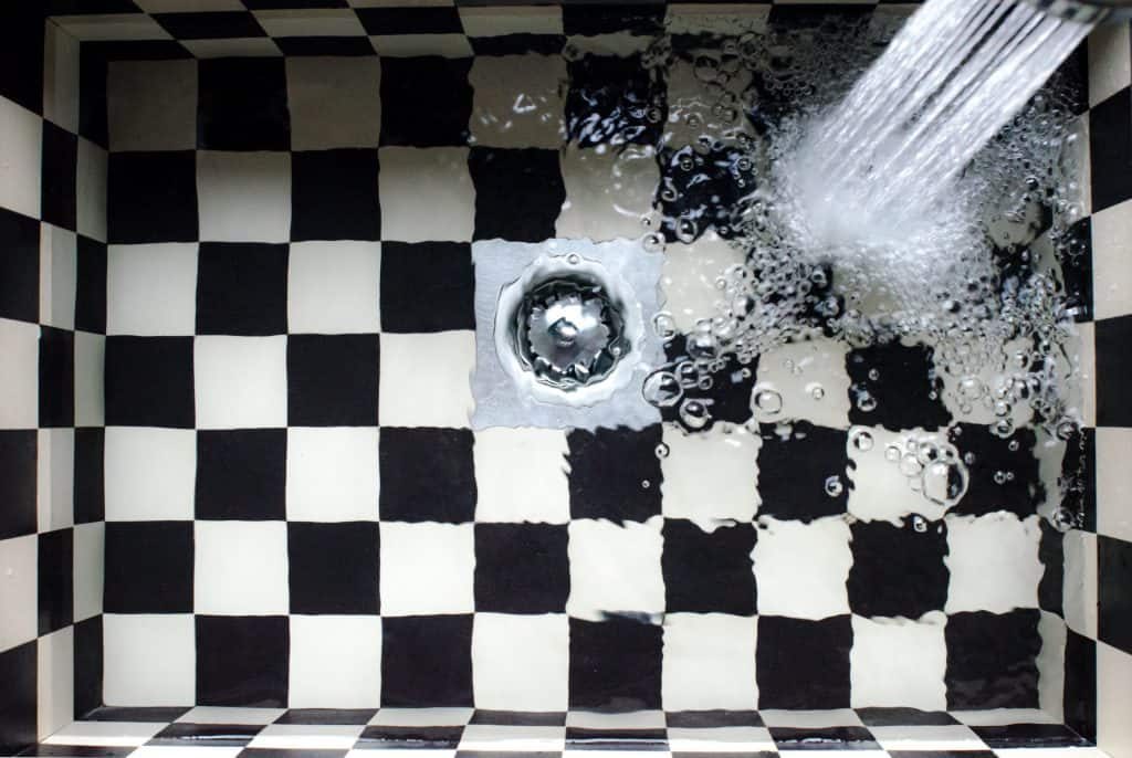 Water flowing in a shower drain with a hair catcher